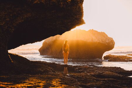 Traveller woman in swimsuit posing at sunset near ocean and rocks in Bali. Woman in bikini and amazing landscape