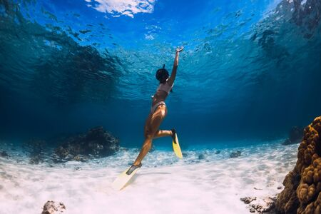 Woman freediver swimming over with yellow fins in blue ocean. Freediving or snorkeling in Mauritius Stock Photo