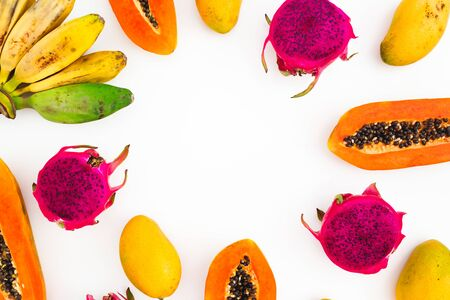 Banana, papaya, mango and dragon fruits on white background. Flat lay. Top view. Tropical fruit frame