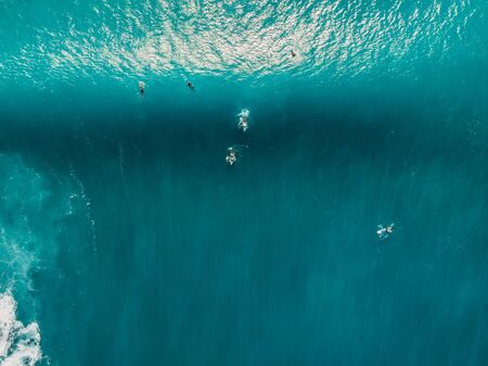 Aerial view of surfers in blue ocean. Top view. Surfing in tropical sea Stock Photo