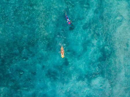 Aerial view of surfers on surfboard in blue ocean. Top view Stock Photo - 144596889