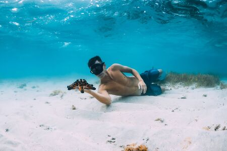Freediver man with hold starfish and relax over sandy bottom in blue ocean