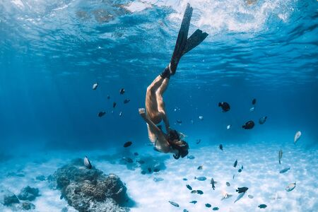 Free diver girl with fins glides over sandy bottom with tropical fishes in blue ocean