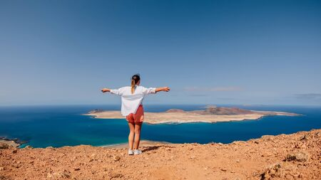 Viewpoint to La Graciosa from Lanzarote and happy traveller woman. View of La Graciosa Island and ocean