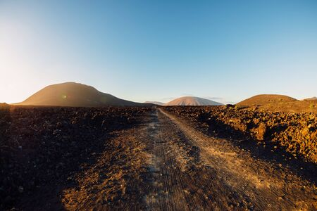 Volcanic landscape with volcanos, dirty road and rocks with sunset tones at Lanzarote, Spain. 版權商用圖片
