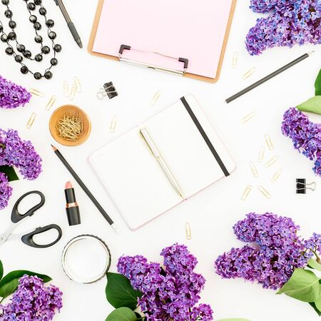 Freelancer workspace with diary, lipstick, scissors, branches of lilac and accessories on white