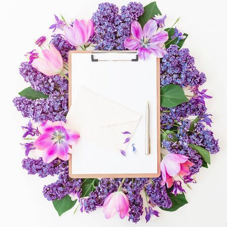 Clipboard with pen, tulips and lilac flowers on white