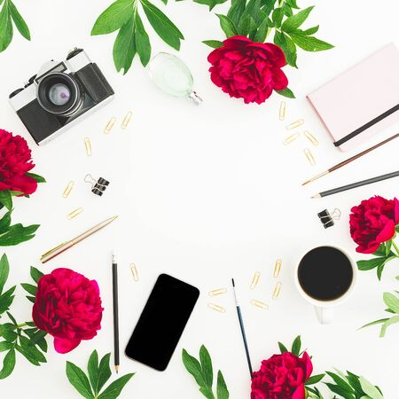 Freelancer workspace with diary, peony flowers, retro camera and smartphone on white