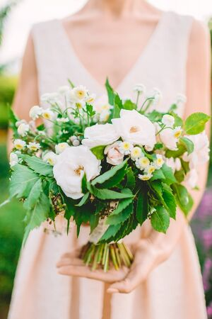 Young woman florist holding in hands flowers bouquet. Stock Photo