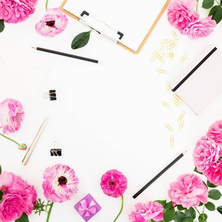 Workspace with clipboard, diary, pink roses and accessories on white Stock Photo