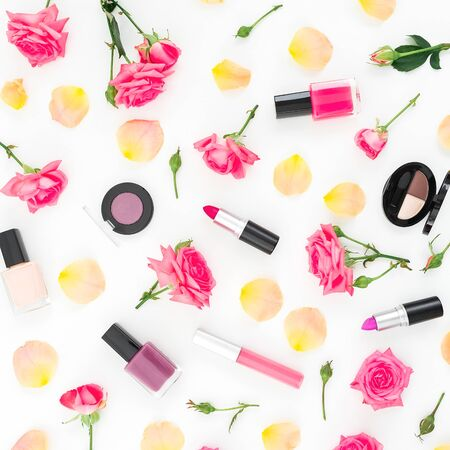 Floral composition with roses flowers and feminine make up cosmetics on white