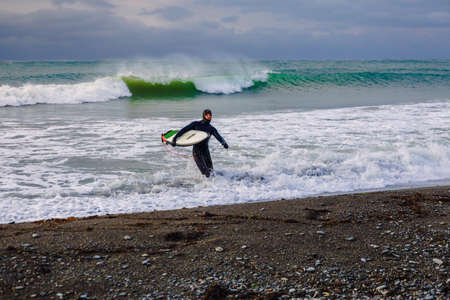 November 22, 2019. Crimea, Russia. Surfer in wetsuit with surfboard at beach.