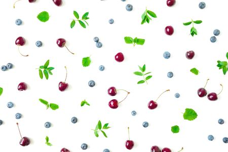 Blueberries and cherry with mint leaves on white background. Top view. Flat lay