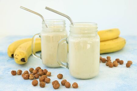 Healthy yogurt or smoothie with banana and nuts, vegetarian food, diet and health concept