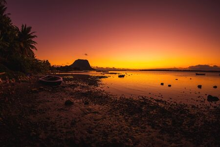Fishing boat, quiet ocean and colorful sunset. Le Morn brabant mountain in Mauritius.