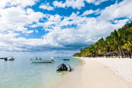 Luxury beach in Mauritius. Transparent ocean with boats, beach, coconut palms and blue sky Stock Photo