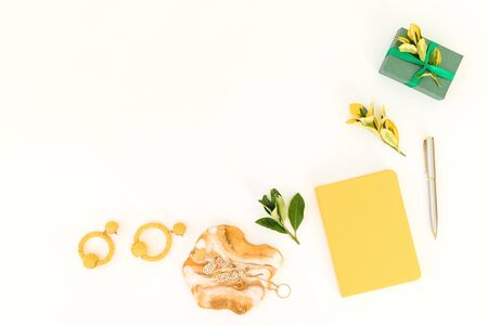 Resin art with yellow diary, gift, pen and leaves on white background. Flat lay, top view Stock Photo