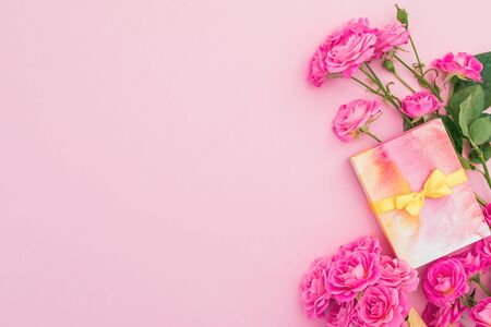 Floral frame with roses flowers and present gift box on pink background. Flat lay, Top view, Stock Photo