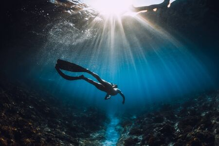 Young freediver woman with fins glides and amazing sun rays. Freediving underwater in sea