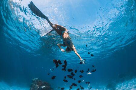 Freediver girl in bikini with fins glides underwater in blue transparent ocean