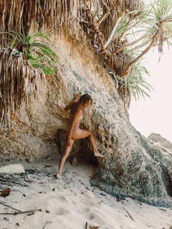 Attractive young woman posing at tropical beach. Wet model