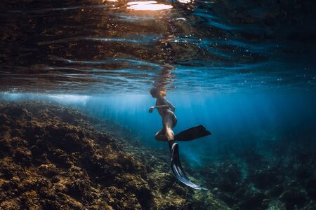 Sporty woman freediver with fins glides underwater in ocean
