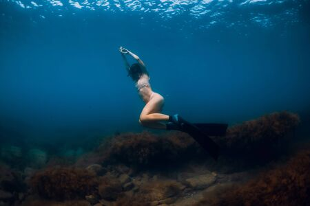 Sporty woman freediver with fins glides underwater in blue ocean. Stock Photo