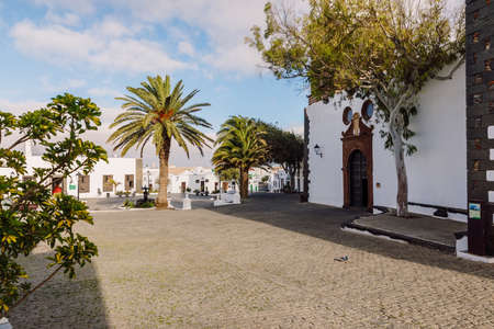 Lanzarote, Spain - April 04, 2020. The old architecture of city of Teguise. Church Iglesia de Nuestra Senora de Guadalupe and palms