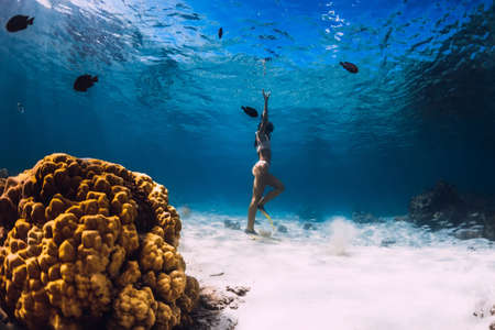 Woman dive underwater with yellow fins in tropical ocean. Freediving or snorkeling in Mauritius