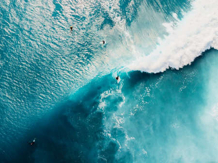 Aerial top view of surfing at barrel waves. Blue waves and surfers in Bali