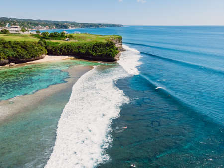 Surfing waves in blue ocean and cliff at background. Aerial view of tropical island with waves