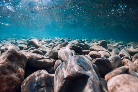 Underwater view with stones and blue transparent sea water.