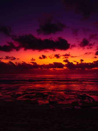 Ocean beach with waves and reflection at bright sunset or sunrise in Bali. Stock fotó
