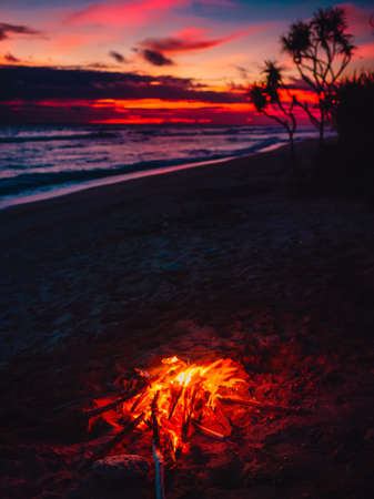 Bonfire on beach with waves and bright sunset or sunrise in Bali.