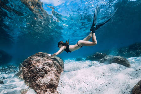 Woman freediver posing over sandy bottom with fins. Freediving in blue ocean at Hawaii islands