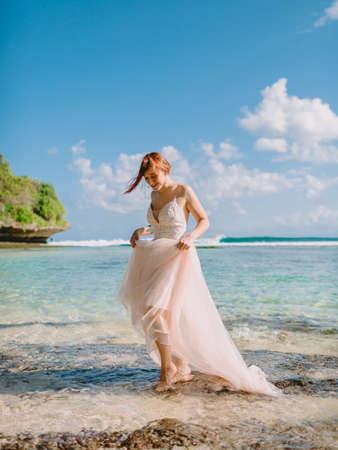 July 5, 2020. Bali, Indonesia. Wedding day of red head bride in wedding dress at tropical beach. Happy wedding in tropical Bali