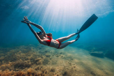 Slim woman in bikini glides at blue sea with sun rays. Freediving with fins underwater in sea Stock Photo