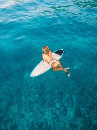 Attractive surfer woman on surfboard in blue ocean. Aerial view Standard-Bild