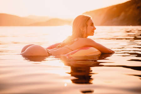Young attractive girl with sexy body relax in the sea at warm sunset Stock Photo