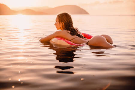 Young attractive girl with sexy body relax in the sea at warm sunset Standard-Bild