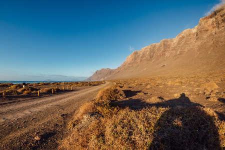 Scenic mountains landscape with dirty road and coastline in Lanzarote, Canary islands