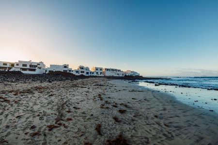 Famara beach and Caleta de Famara town with sunset tones in Lanzarote, Canary islands