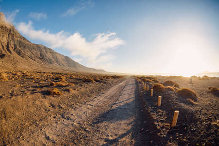Famara coastline, landscape with dirty road and mountains in Lanzarote, Canary islands