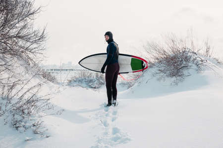 Winter and surfer with surfboard. Snowy beach with male surfer in wetsuit.