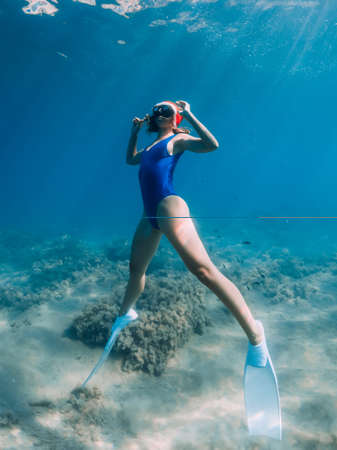 Happy freediver woman with New year cap glides underwater in blue ocean. Christmas holidays concept