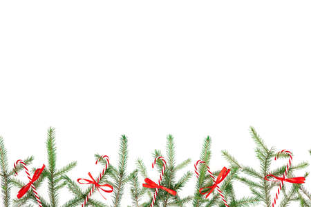 Christmas frame made of fir branches and red decoration on white background. Flat lay, top view. Copy space Standard-Bild