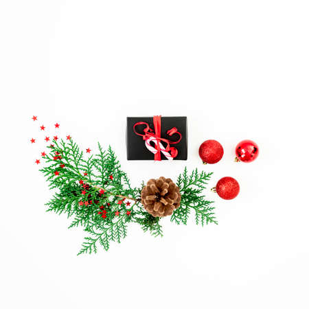 Merry Christmas composition with green branches, gift and red balls with confetti on white background. Flat lay, top view
