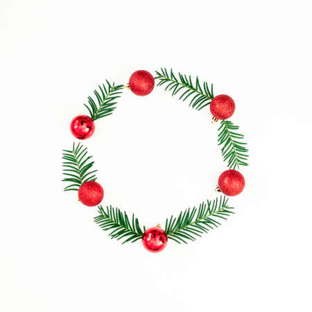 Christmas frame of evergreen branches and red balls on white background. Flat lay, top view