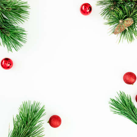 Christmas frame of pine branches and red balls decoration with confetti on white background. Flat lay, top view Standard-Bild