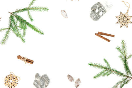 Christmas frame of fir branches and cinnamon with decor on white background. Flat lay Zdjęcie Seryjne